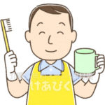 歯ブラシを持つエプロンの男性